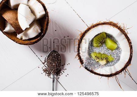 Chia seeds pudding with kiwi fruits in the shell of a coconut on white wooden background. Flat lay.