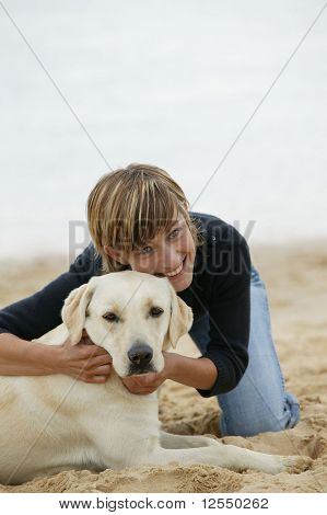 Young woman with a dog on the beach