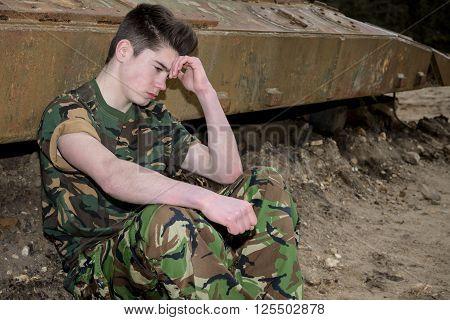 Teenage soldier looking depressed sitting by a ruined tank