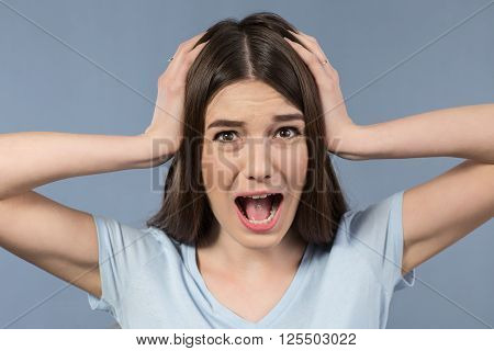 What to do. Attractive horrified young girl holding her hands on the head and expressing fear while standing isolated on grey background