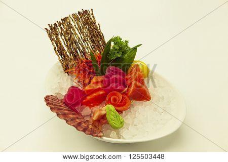 Set of sashimi with the Norwegian salmon and the Atlantic tuna on ice with a fresh Sicilian lemon