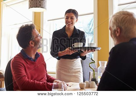 Waitress bringing coffees to a male couple at a restaurant
