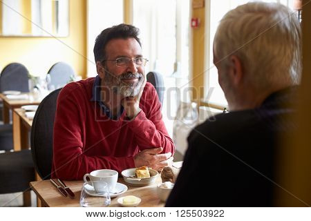 A middle aged gay male couple having lunch in a restaurant