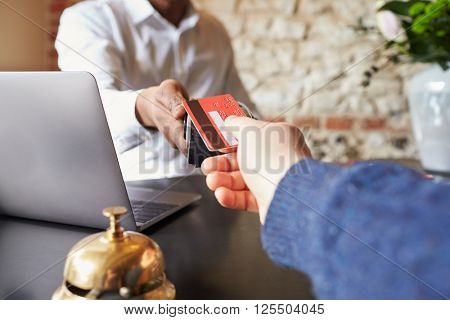 Guest makes card payment at check-in desk of hotel, detail