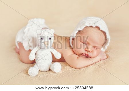 Cute newborn baby in a white knitted hat and white knit panties,with their legs and putting the handle under his cheek,sleeping sweetly on a soft beige blanket with Teddy bear