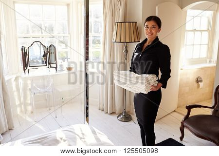Chambermaid carrying fresh linen into a hotel bedroom