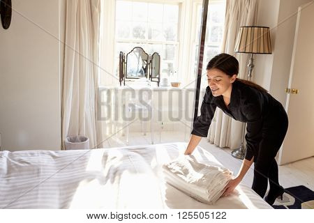 Chambermaid placing fresh linen on to a bed in a hotel room