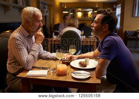 Middle aged male couple having evening meal in a restaurant