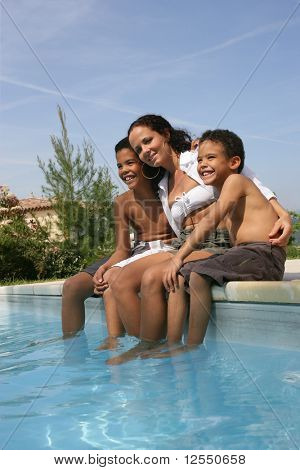 Portrait of a young woman and two young boys sitting at a poolside