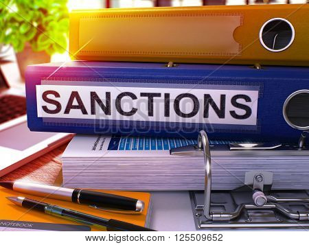 Sanctions - Blue Office Folder on Background of Working Table with Stationery and Laptop. Sanctions Business Concept on Blurred Background. Sanctions Toned Image. 3D.