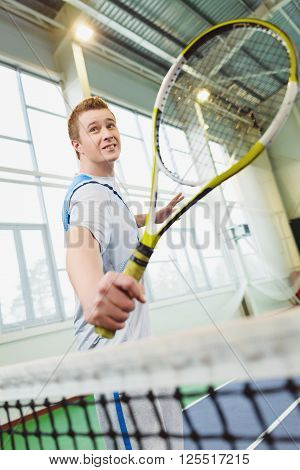 Low angle view of determined young man playing tennis indoor. ** Note: Shallow depth of field