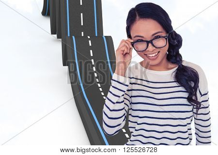Smiling Asian woman holding eyeglasses against blue background
