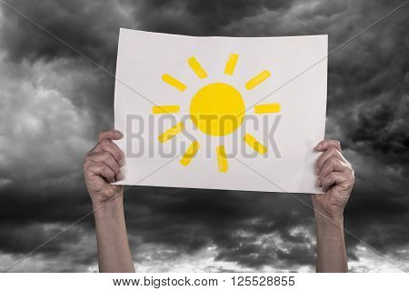 Hands holding a piece of paper with a painted sun high in front of dark clouds.