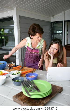 Portrait of a senior woman cooking next to a young woman with a laptop computer