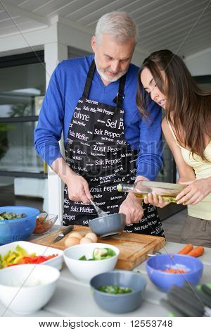 Portrait of a senior man cooking with a young woman