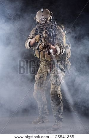 Portrait of US Army Soldier in Action with Four-eyed night vision goggles in the Smoke; Dark and Foggy Background; Beam of light