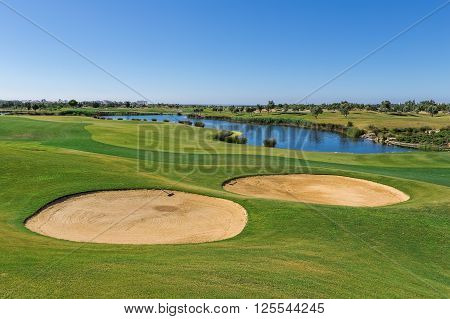 Sand trap on the golf course. Lake in the background.