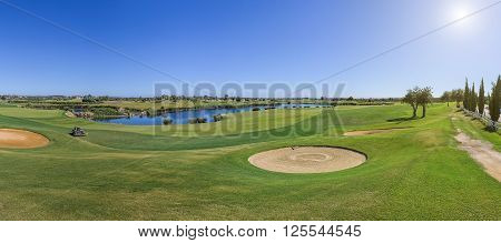 Panorama of a golf course on a sunny day. Sand traps.