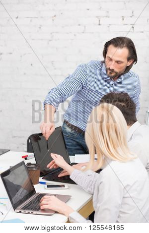 Coworking of businessteam in office. Handsome business man in blue shirt showing business characteristics to his colleagues.
