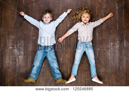 Happy children. Top view creative photo of little boy and girl on vintage brown wooden floor. Children looking at camera and smiling