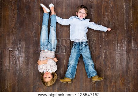 Happy children. Top view creative photo of little boy and girl on vintage brown wooden floor. Boy holding girl's leg. Girl is upside down