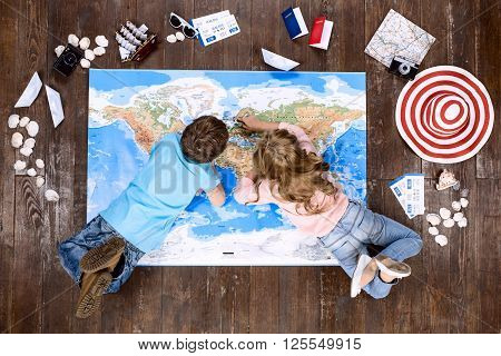 Happy children. Top view creative photo of little boy and girl on vintage brown wooden floor. Children lying on world map near travel things