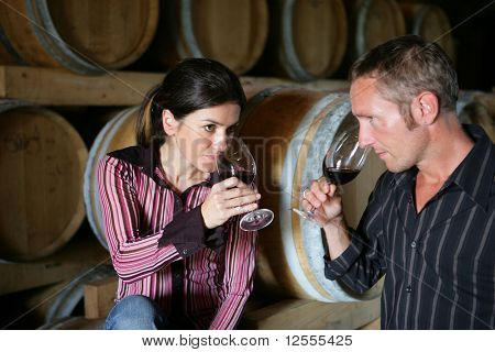 Man and woman tasting a glass of red wine