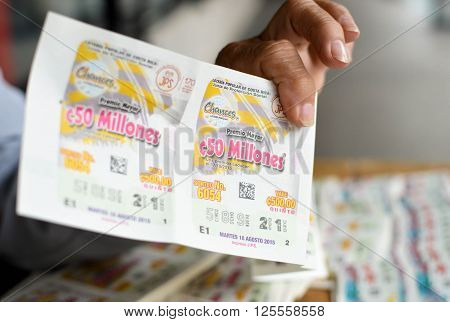 San Jose Costa Rica - August 18 2015: Hand holds the lottery ticket in San Jose. Shallow DOF. The text in Spanish says: popular lottery of Costa Rica Party of social protection big prize of 50 million colones costs 500 colones