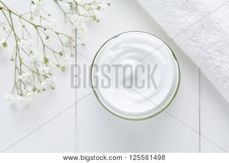 Natural cosmetic cream skincare product wellness and relaxation makeup mask in glass jar with towel on white background
