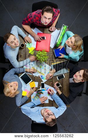 Top view creative photo of business people sitting at dark wooden vintage table. Business people having meeting. Concept for successful teamwork. There are electronic gadgets. People looking at camera