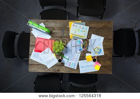 Top view creative photo of dark wooden vintage table full of graphics. Objects after meeting. Concept for successful teamwork
