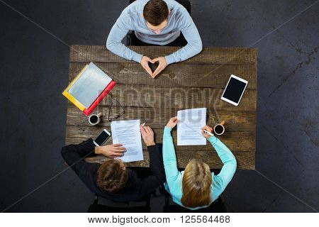 Top view creative photo of business people sitting at dark wooden vintage table. Employers having meeting. Concept for successful interview. There are electronic gadgets and documents at table