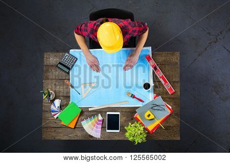 Top view creative photo of engineer sitting at dark wooden vintage table. Architect with helmet working with blueprints