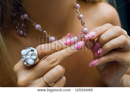 woman puts on a necklace