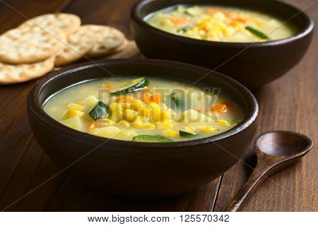 Vegetarian corn and courgette chowder served in rustic bowls saltine cracker in the back photographed on dark wood with natural light (Selective Focus Focus one third into the soup)