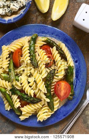 Baked green asparagus cherry tomato and rotini pasta salad served on plate with blue cheese and lemon wegde on the side photographed overhead on slate with natural light