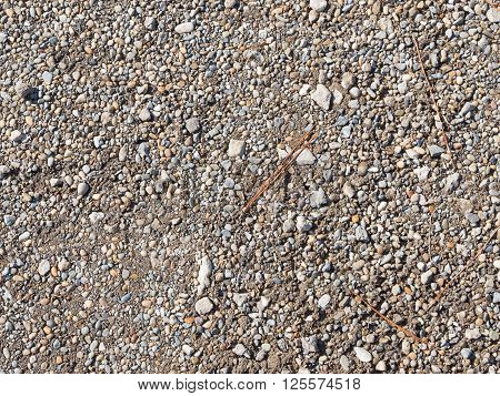 small granite gray and brown old gravel as ballast lying on the street and dry pine needles