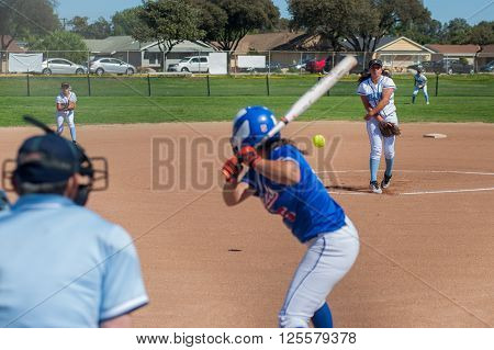 Softball pitcher throwing the curve ball to the batter.
