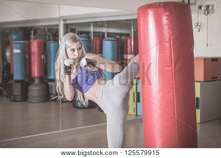 Fighter woman hits the heavy bag with a side kick