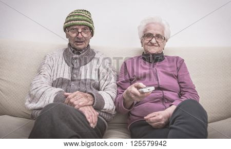 Old couple and zapping. senior couple watching television on the couch