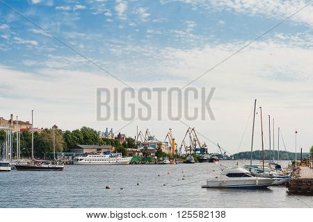 Sea port of Vyborg town. Passanger ships port cranes and sailing yachts. Russia.