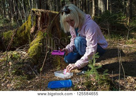 A woman geocaching in a green forest ** Note: Visible grain at 100%, best at smaller sizes