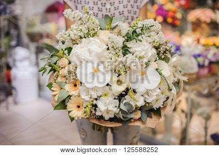 big white bouquet with huge orchids in woman hands