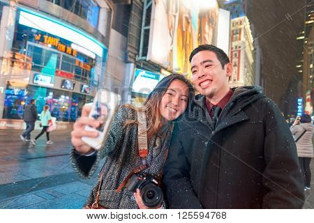 NEW-YORK - CIRCA MARCH 2016: people taking a selfie. A selfie is a self-portrait photograph, typically taken with a digital camera or camera phone held in the hand or supported by a selfie stick.