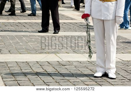 Lower body of officer in white uniform who holds carnation flowers on Victory Day celebration at the Museum of The History of Ukraine in World War II in Kyiv, Ukraine