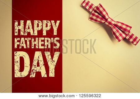 Happy Father's Day. Red cell bow tie on beige background