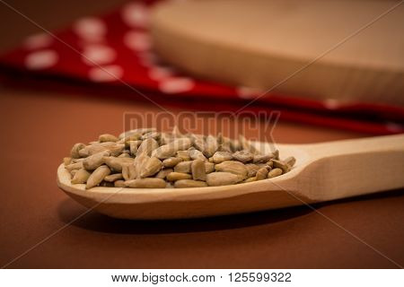 Sunflower seeds on a wooden spoon on the table