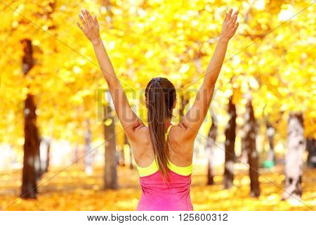 Young beautiful woman doing sport exercises in autumn park poster