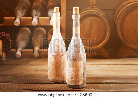 Aged wine bottles in a wine cellar on wooden table