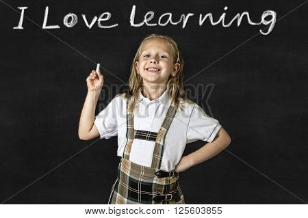 young sweet junior schoolgirl with blonde hair standing happy and smiling isolated in front of classroom blackboard holding chalk wearing school uniform in children education success and fun